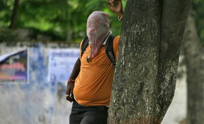 A journalist covers his face to avoid tear gas smoke thrown by police towards Telangana supporters..