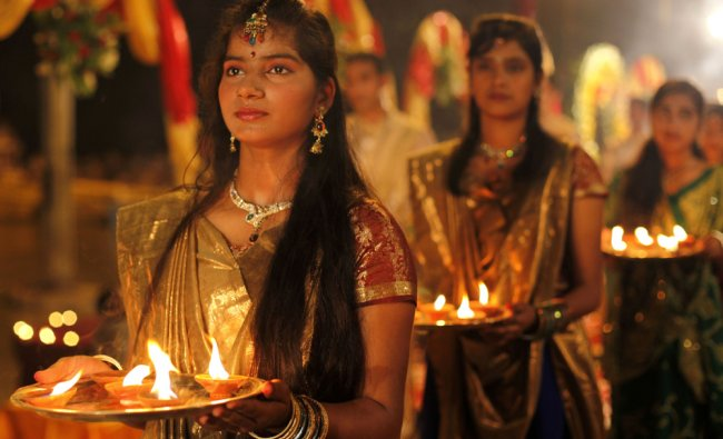 Hindu devotees hold plates with earthen lamps during a prayer ritual in Varanasi