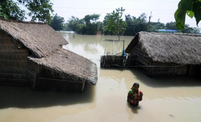 An Indian resident walks through floodwaters beside her home