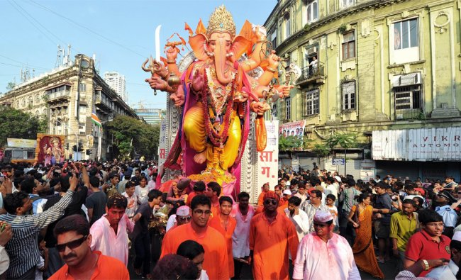 Indian Hindu devotees walk during a procession for immersion of a huge idol of the elephant-headed..