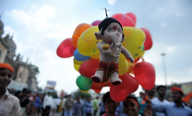 Hindus carry a stuffed toy doll of the elephant-headed god Lord Ganesha tied with balloons...