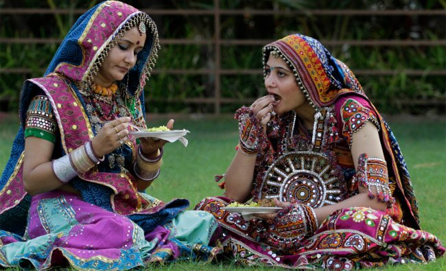 Indian women in traditional attire have breakfast after a practice session of Garba