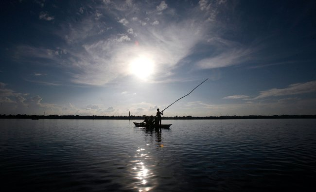 A boat is silhouetted against the setting sun before the start of an annual boat race