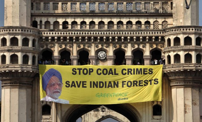 Greenpeace activists hang a banner with a photo of Indian PM Manmohan Singh atop the Charminar