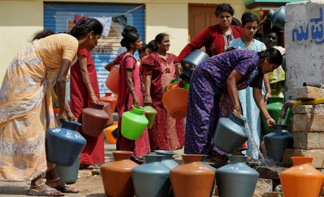 Indian residents facing drinking water shortage wait with plastic pots at a tube well