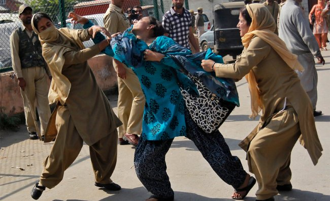 A member of the National Youth Corps (NYC) scuffles with Indian police women