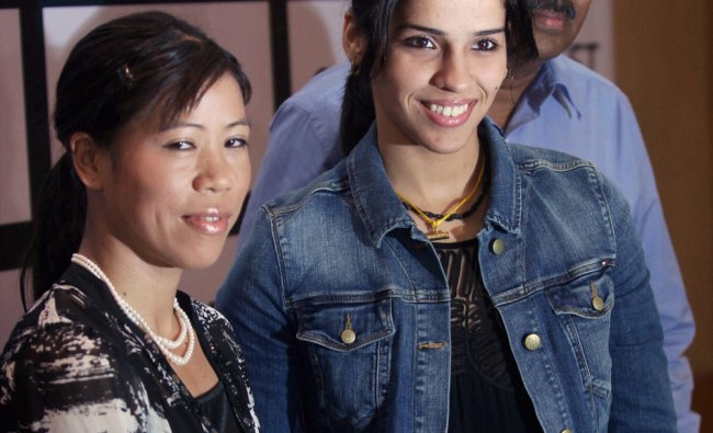Olympic medal winners Saina Nehwal and MC Mary Kom pose for a photo after their felicitation at ...