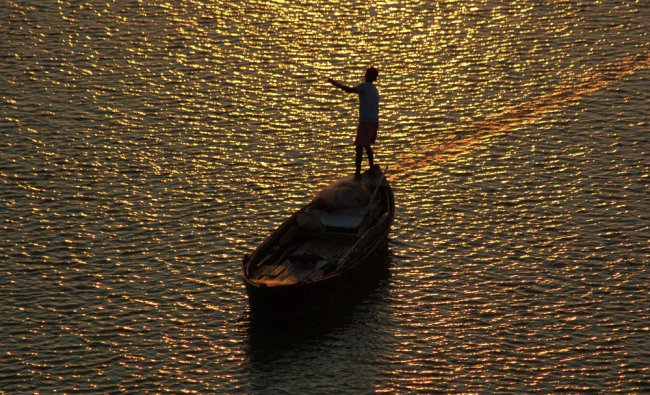A fisherman casts his net in Ganga river during sunset in Mirzapur