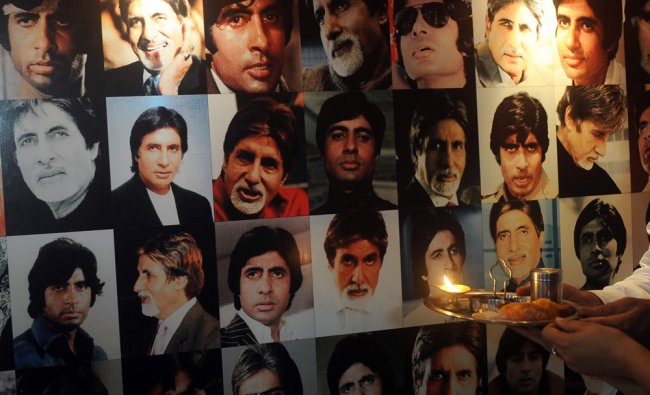 A fan of Indian Bollywood actor Amitabh Bachchan performs a prayer in front of a banner