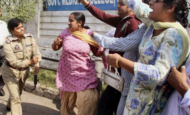 A police woman charging Jammu & Kashmir Democratic Front (JKDF) activists who were protesting...
