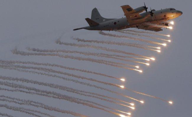 A Japanese Maritime Self-Defense Force (JMSDF) P3C anti-submarine patrol plane fires flares...