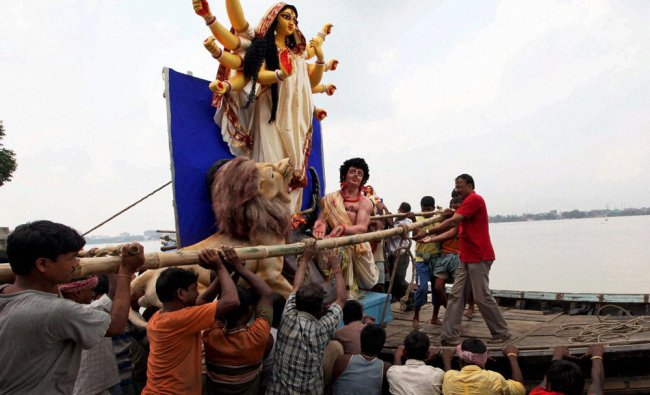 Idol of Goddess Durga being lifted onto a boat on the river Ganga ahead of upcoming Durga Puja...