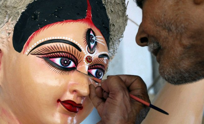 An artist gives a finishing touch to a Durga idol ahead of the Durga Puja festival in Guwahati on...
