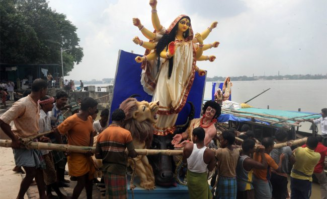 Indian labourers carry a finished clay statue of Hindu goddess Durga from a workshop in Kumartoli...