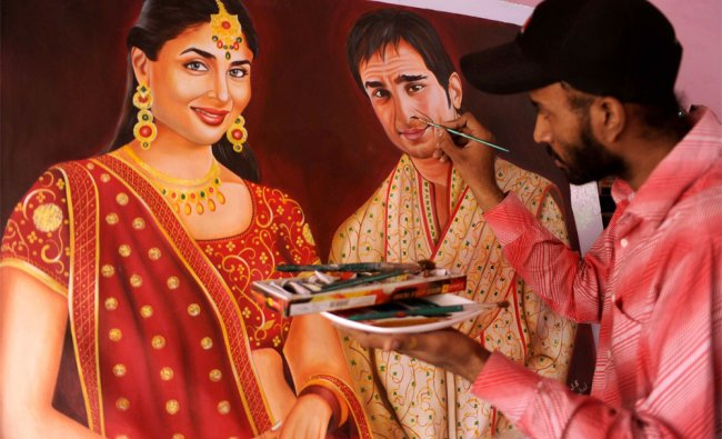 Indian painter Jagjot Singh Rubal finishes off a painting of Bollywood film actors Saif Ali Khan...