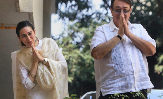 Actor Randhir Kapoor and Karishma wave to fans as they come out after attending the wedding..