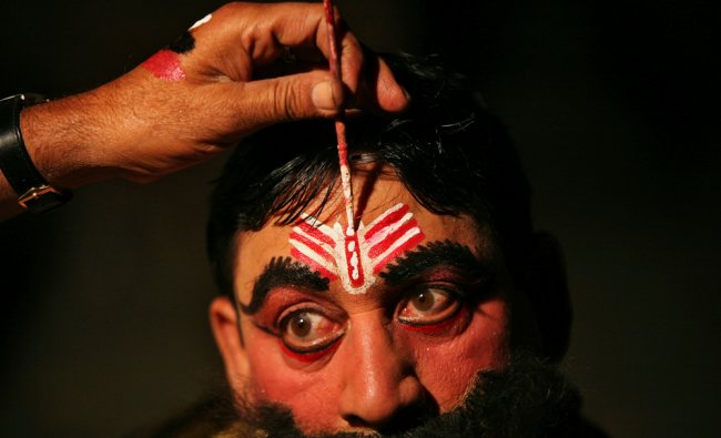 An artist gets makeup applied backstage before performing the role of the demon king Ravana
