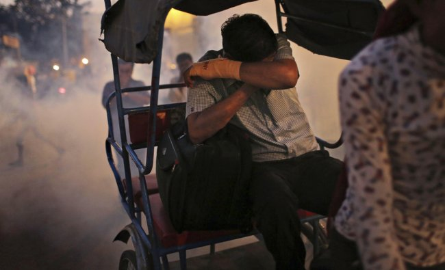 A man covers his face as he rides in the back of a rickshaw