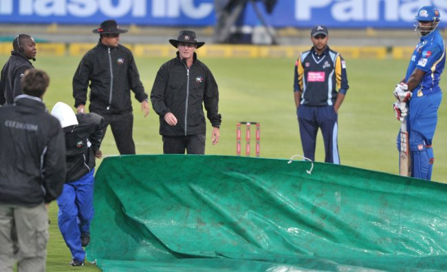 Groundsmen prepare the covers as rain delayed play during Match 11 of The Champions League T20...