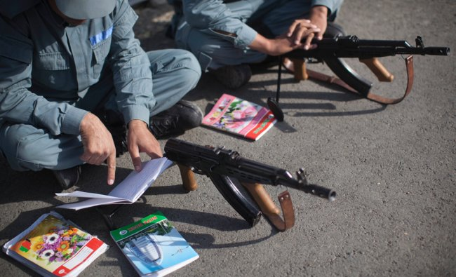 Afghan National Police recruits study their notes on how to use a Kalashnikov rifle