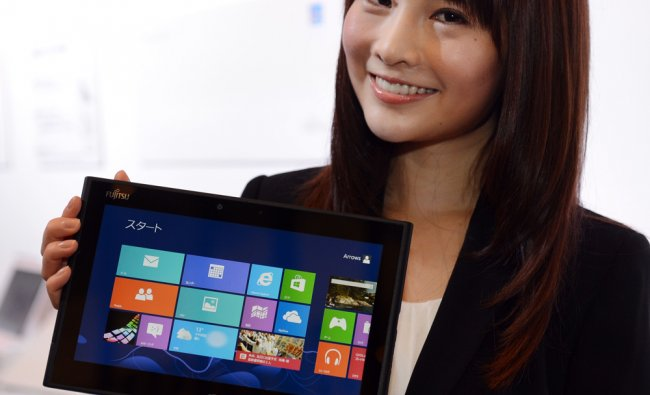 A model shows off Fujitsu\'s latest Windows 8 water-proof tablet PC, \'ARROWS Tab