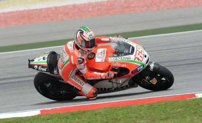 Nicky Hayden of the US speeds around the corner during the first practice session