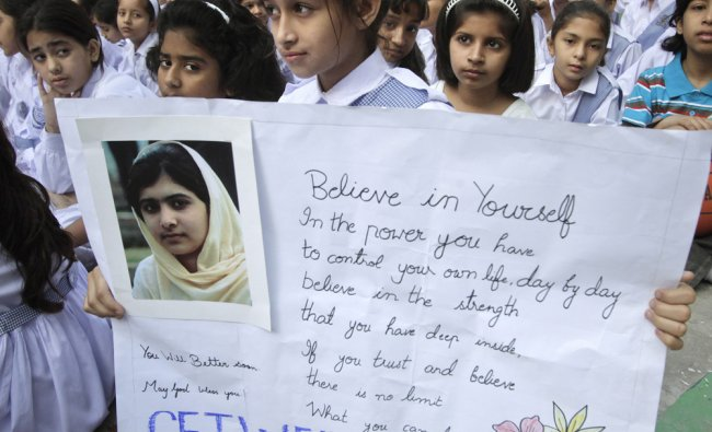 A student holds a placard during special prayers for the recovery of Malala Yousufzai
