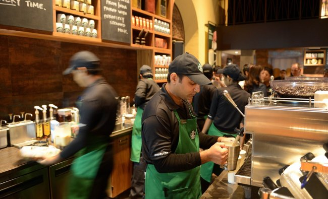 Staff work behind the counter of India\'s first newly-inaugurated Starbucks outlet