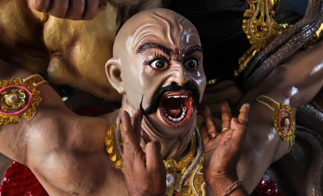 An artist pastes mustaches on to a clay model of a devil for the upcoming Durga Puja festival