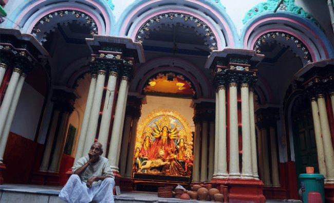 An Indian man waits for a priest infront of an idol of Hindu goddess Durga displayed...