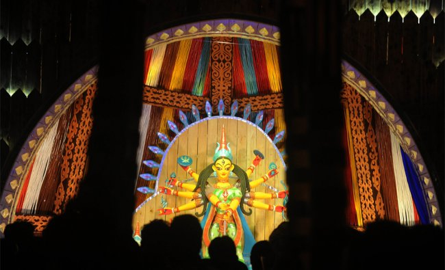 Indian visitors look at an idol of Hindu goddess Durga in preparation for the upcoming...