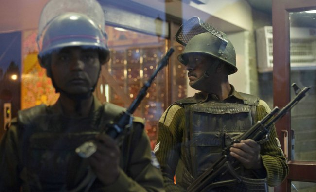 Indian paramilitary soldiers stand guard at the entrance of a hotel where suspected militants opened