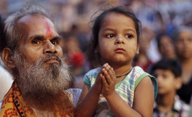 A devotee carries a young girl as they watch a Dussehra procession