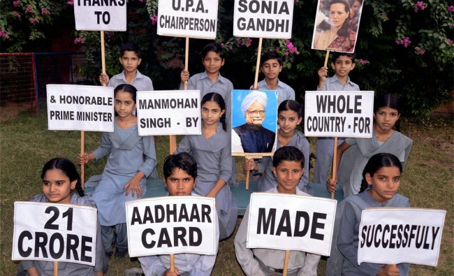 Children hold placards to thank Manmohan Singh and Sonia Gandhi for Adhaar Card in Jodhpur...r