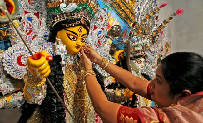 A woman decorates an idol of Goddess Durga ahead of \'Mahasasthi\' puja
