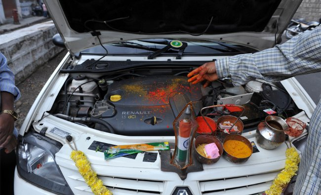 A Hindu priest performs Ayudha Puja on a devotee\'s vehicle in Hyderabad...