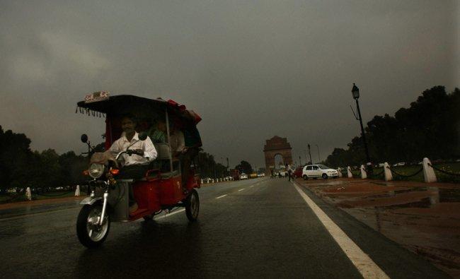 A battery-operated rickshaw plying at Rajpath during rains in New Delhi