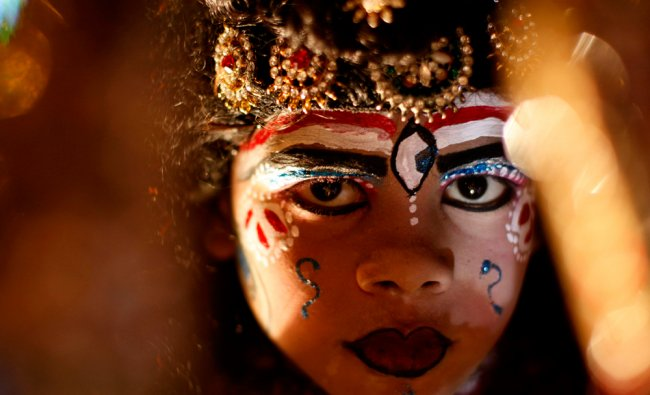 A Young artist dressed as Hindu god Shiva participates in a Dussehra procession
