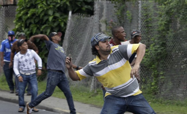 A man throws a stone at riot police during an ongoing violent protest in Colon City