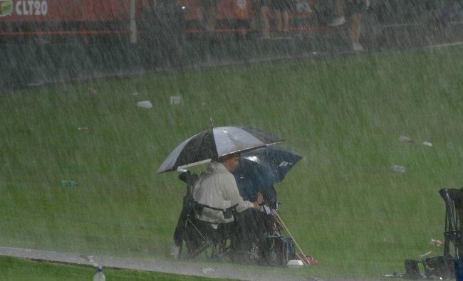 South African cricket fans wait as rain pours before a Champions League T20...
