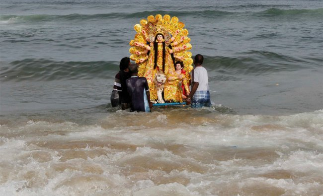 Devotees carry an idol of the Hindu goddess Durga to immerse it into the sea at the Marina beach