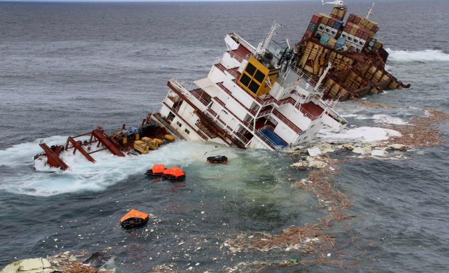 Debris floats around the remains of the stricken container ship Rena as it submerges
