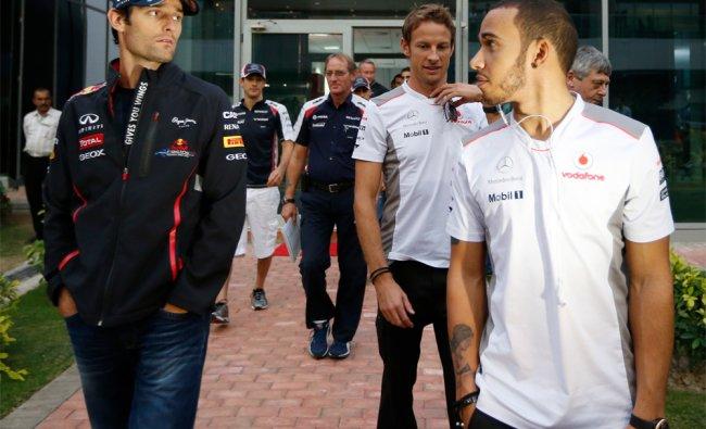 Red Bull driver Mark Webber of Australia walks with McLaren drivers Jenson Button and Lewis Hamilton