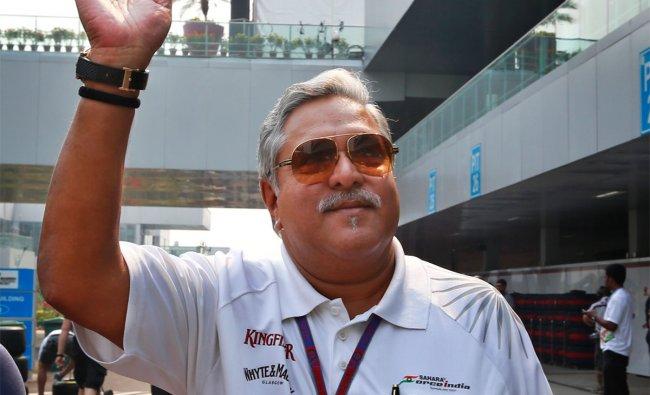 Force India team principal and businessman Vijay Mallya waves as he walks down the F1 paddock