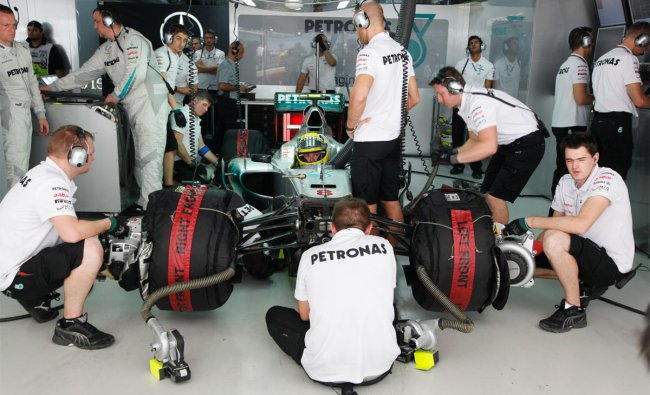 Mercedes driver Nico Rosberg of Germany waits in his car as his mechanics work on it