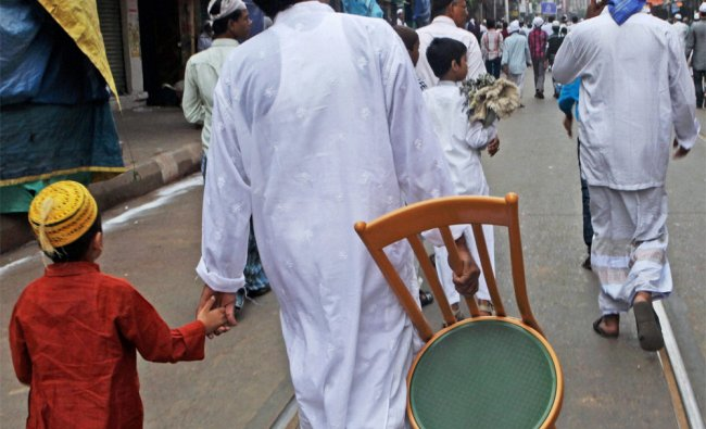 A muslim carries his chair while returning home after offering namaz on the occasion of Id-ul-Zuha