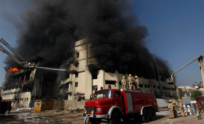 Firemen try to extinguish a fire at the chemical warehouse of a plastic bag factory in Pakistan...