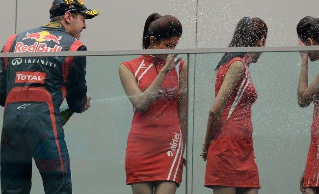 Winner Red Bull Renault driver Sebastian Vettel sprays champagne at Indian grid girls...