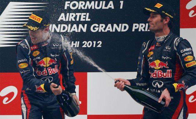 Third placed Red Bull driver Mark Webber sprays champagne on teammate and winner Sebastian Vettel.