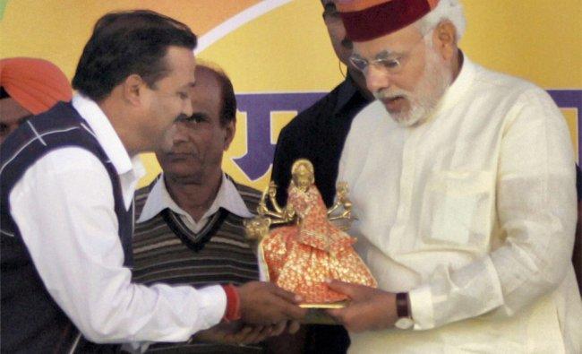 : BJP candidate Sanjay Chaudhary presents an idol of Ma Brijeshwari to Chief Minister of Gujarat...